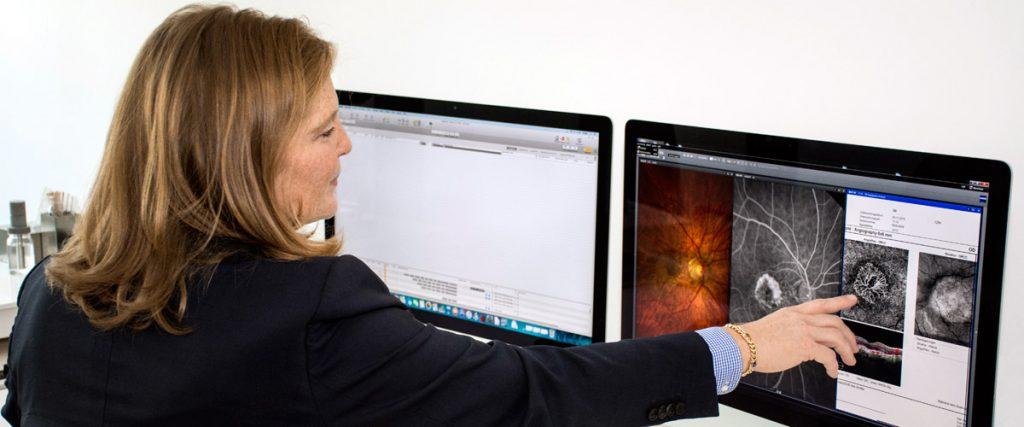 Augenärztin Dr. Brusis erklärt die Augenerkrankung Makula-Degeneration und Behandlungsmöglichkeiten anhand von Fotos am Bildschirm.